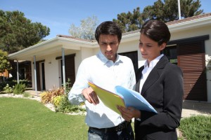 Estate-agent stood with client outside house